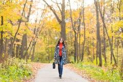 秋天概念-走本质上的美丽的年轻现代妇女 免版税库存照片