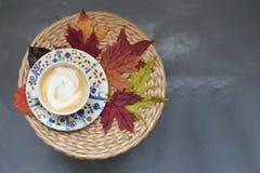 秋天概念Coffe杯子槭树离开柳条桌秋季C 免版税库存照片