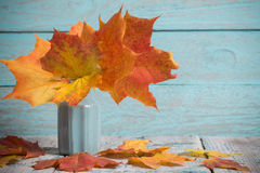 秋天槭树在花瓶把束留在木背景 免版税库存照片