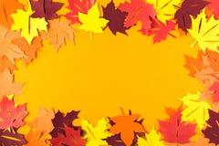 秋天槭树框架在橙色纸离开 平的位置 顶视图 复制空间 纸裁减样式 库存照片