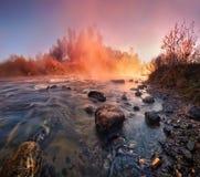 秋天横向 在河的火热的意想不到的日出有雾和岩石的 免版税图库摄影