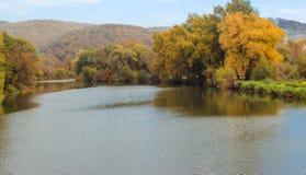 秋天河和五颜六色的树在水附近 免版税库存照片