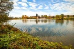 秋天河,在水附近的五颜六色的树在村庄 库存照片
