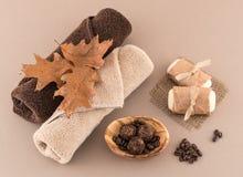 秋天温泉用咖啡巴恩炸弹、肥皂和豪华毛巾 库存图片