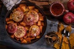 秋天甜盘烘烤了苹果和南瓜在一个煎锅用蜂蜜在土气背景 顶视图 图库摄影