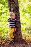 秋天男婴在树附近站立,回顾森林 图库摄影