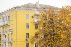 秋天的典型的斯大林ampir样式房子,围拢由与橙色叶子的树 免版税库存图片