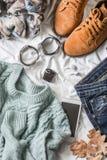 秋天的平的位置妇女` s衣物走,顶视图 布朗绒面革起动,牛仔裤,一件蓝色套头衫,围巾,镯子,手表, headp 图库摄影
