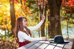 秋天的拍selfie自已照片的森林公园美丽的妇女 图库摄影