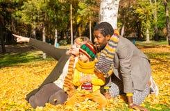秋天系列愉快的公园 非裔美国人的家庭:自然的黑人父亲、妈妈和儿童男孩在秋天 免版税库存照片