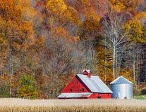 秋天红色谷仓和山坡 库存照片