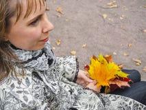 秋天美丽的公园妇女 妇女在有五颜六色的槭树的秋天公园离开 翠菊许多秋天的紫红色心情粉红色 免版税库存照片