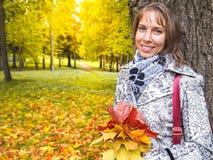秋天美丽的公园妇女 妇女在有五颜六色的槭树的秋天公园离开 翠菊许多秋天的紫红色心情粉红色 免版税图库摄影