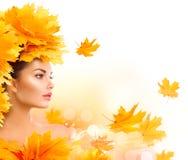 秋天美丽的日秋天森林走的妇女 有秋天明亮的叶子发型的秀丽式样女孩 库存照片