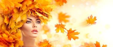 秋天美丽的日秋天森林走的妇女 有秋天明亮的叶子发型的秀丽式样女孩 库存图片
