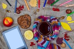 秋天背景概念:热的茶、片剂、叶子和色的p 库存照片