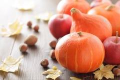 秋天背景用南瓜北海道,苹果、坚果和叶子在木桌上 免版税库存照片