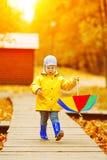 秋天背景的小男孩  有彩虹伞的公园我 库存照片