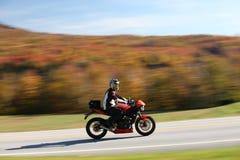 秋天背景的高速摩托车骑士 免版税库存图片