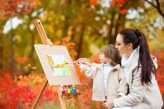 秋天自然、妈妈和女儿在秋叶公园绘一幅画,绘一个小孩,儿童创造性 库存照片