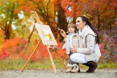 秋天自然、妈妈和女儿在秋叶公园绘一幅画,绘一个小孩,儿童创造性 库存图片