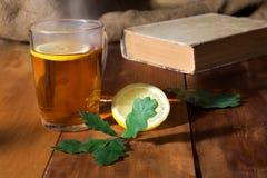 秋天茶用在旧书的柠檬与在木背景的叶子 免版税图库摄影