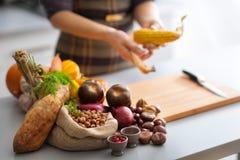 秋天菜在一个厨房里用匿名妇女剥壳的玉米 免版税图库摄影