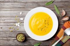 秋天菜或南瓜汤与种子在白色碗在木土气台式视图 库存图片