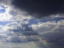 秋天蓝天,太阳通过雨云发光 免版税库存图片