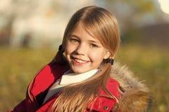 秋天衣裳和时尚概念 儿童白肤金发的长发走的秋天公园背景 感觉愉快的晴朗的秋天天 ?? 免版税库存图片