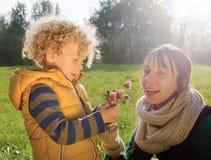 秋天衣裳的小男孩给他的妈妈一朵花,特写镜头 图库摄影