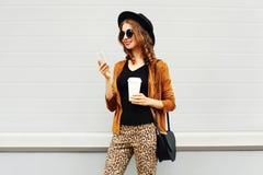 秋天豪华神色,相当有咖啡杯的凉快的微笑的少妇使用智能手机走在城市,愉快的女性模型的 免版税库存图片