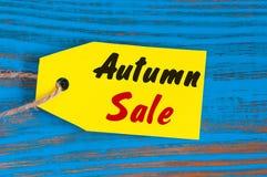 秋天销售,在蓝色木背景的价牌 库存照片