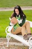 秋天长凳书公园读了妇女年轻人 免版税库存照片