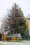秋天雪剥落落在灰色木停放的推车 免版税库存图片