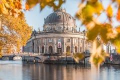 秋天震动的预示的博物馆与叶子和河狂欢与桥梁 免版税库存照片