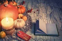秋天静物画用南瓜、灼烧的蜡烛和笔记薄,温泉 免版税图库摄影