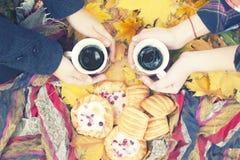 秋天静物画,两个杯子用茶在手,蛋糕,野餐上在秋天公园 库存照片