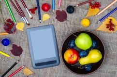 秋天静物画:苹果、黄色叶子、片剂和色的笔 图库摄影