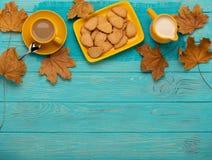 秋天静物画-咖啡用以叶子o的形式一个曲奇饼 图库摄影