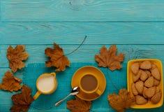 秋天静物画-咖啡用以叶子o的形式一个曲奇饼 库存图片