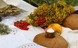 秋天静物画-大面包,南瓜,山脉灰,艾菊,麦子耳朵,盐,在与鞋带的一张白色桌布 免版税库存照片