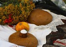 秋天静物画-大面包,南瓜,山脉灰,艾菊,麦子耳朵,盐,在与鞋带的一张白色桌布 库存图片
