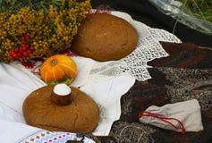 秋天静物画-大面包,南瓜,山脉灰,艾菊,麦子耳朵,盐,在与鞋带的一张白色桌布 免版税库存图片