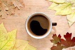 秋天静物画-一杯大咖啡在秋天之前围拢的一张木桌上的上色了叶子 顶视图 免版税库存照片