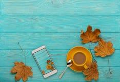 秋天静物画-与叶子和手机的咖啡有p的 库存照片