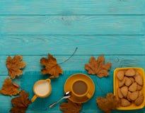 秋天静物画-咖啡用以叶子o的形式一个曲奇饼 免版税图库摄影
