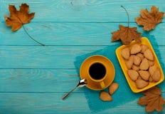 秋天静物画-咖啡用以叶子o的形式一个曲奇饼 库存照片