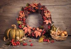 秋天静物画用南瓜、花圈和葱在木头 免版税库存图片