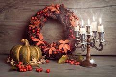 秋天静物画用南瓜、莓果花圈和蜡烛 图库摄影